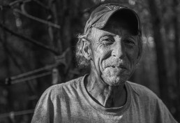 A black and white, environmental portrait of Donnie, a homeless man living behind a Walmart in North Carolina